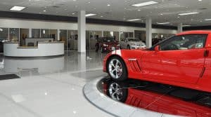 Entry desk of the Ed Bozarth Chevrolet in Aurora. The floor is reflective and white with a red sports car. Designed by D2C Architects Inc.