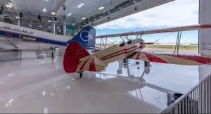 A biplane sitting in the open hangar of the Wings of the Rockies, Blue Sky Gallery designed by D2C Architects