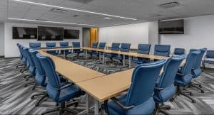 Training and Emergency Operations Center Conference room with a large table in the center that can be multi-functional depending on the use of the room. Blue chairs sit around the outside of the table.
