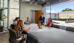 A group of City of Westminster greenhouse employees meet in a large conference room. The garage door to the conference room is open to the outside courtyard.